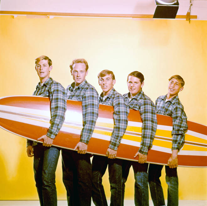 The Beach Boys pose for a portrait with a surfboard in August 1962 in Los Angeles, California