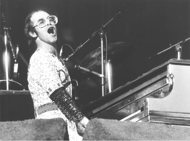 "Elton John and a ""gang"" of friends including Bernie Taupin, manager Ray Williams, producer Steve Brown, roadie Bob Stacey flew to Los Angeles for Elton to make his debut at the famous Troubadour club. Pictured in 1974"